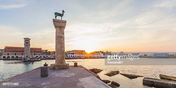 Greece, Rhodes, entrance to Mandraki harbour at sunset