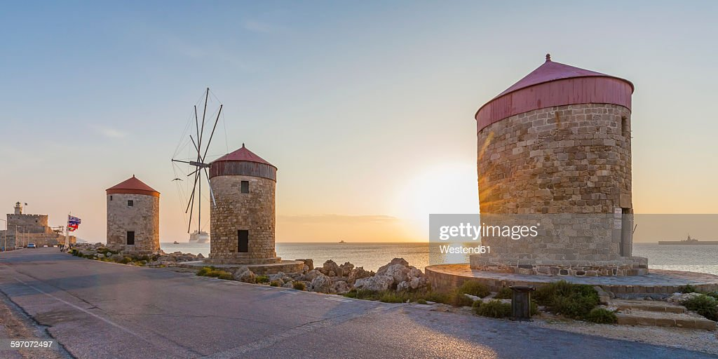 Greece, Rhodes, mole of Mandraki harbour with windmills at sunset : Stock Photo