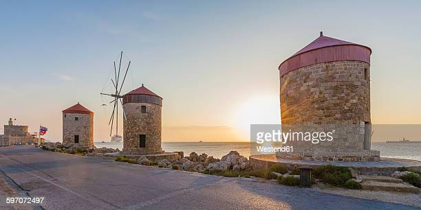 Greece, Rhodes, mole of Mandraki harbour with windmills at sunset
