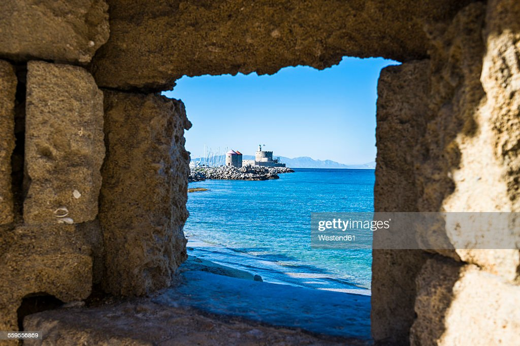 Greece, Rhodes, View through a window at the coast to the okld town : Stock Photo
