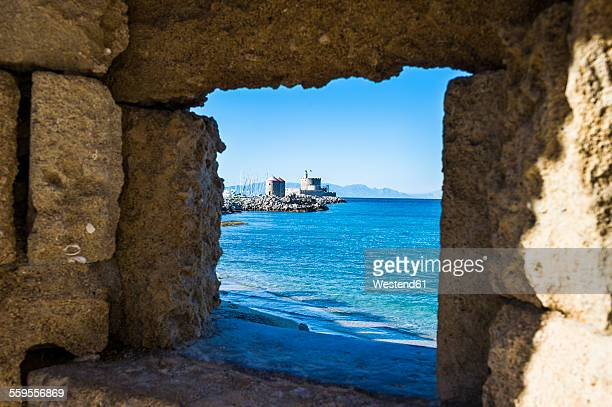 Greece, Rhodes, View through a window at the coast to the okld town
