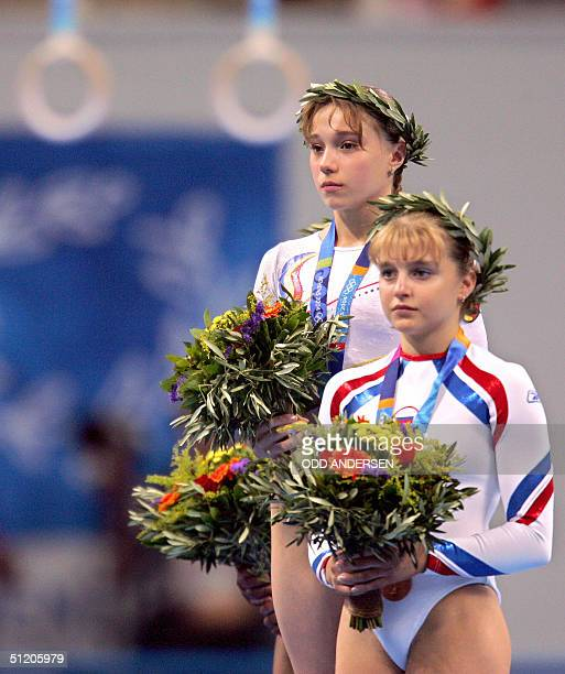 Romanian gold medallist Monica Rosu and Russian bronze medallist Anna Pavlova celebrate on the podium after the women's vault final 22 August 2004 at...
