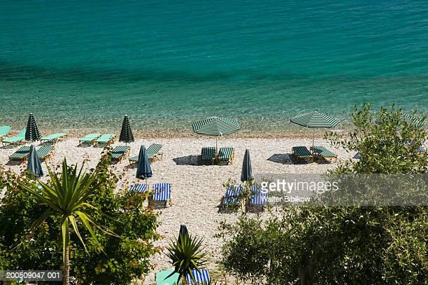 greece, samos, kokkari, tsamadou beach, sun loungers, elevated view - samos stock photos and pictures
