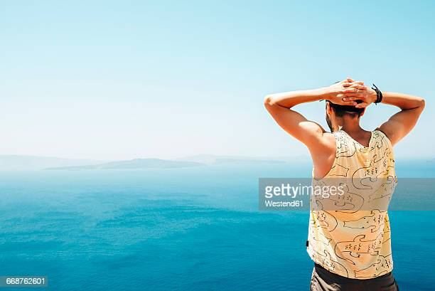 Greece, Santorini, back view of man with hands behind his head looking to the sea