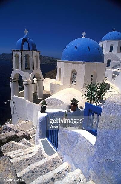 greece, santorini, blue domed buildings of oia village - greek orthodoxy stock pictures, royalty-free photos & images