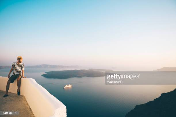 greece, santorini, fira, man on holidays enjoying the sunset over the sea - santorini stock pictures, royalty-free photos & images