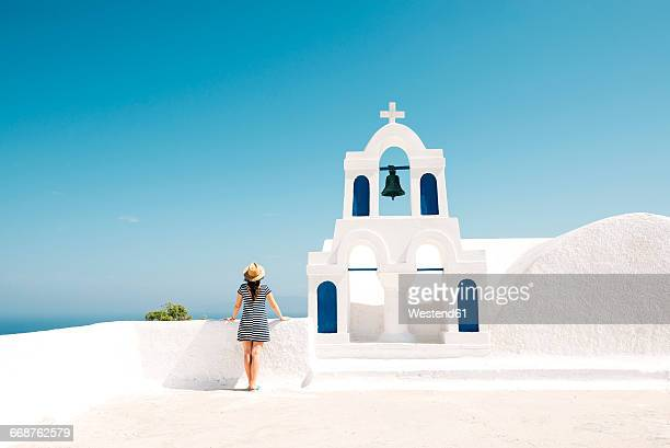greece, santorini, oia, back view of woman standing next to bell tower looking to the sea - islas griegas fotografías e imágenes de stock