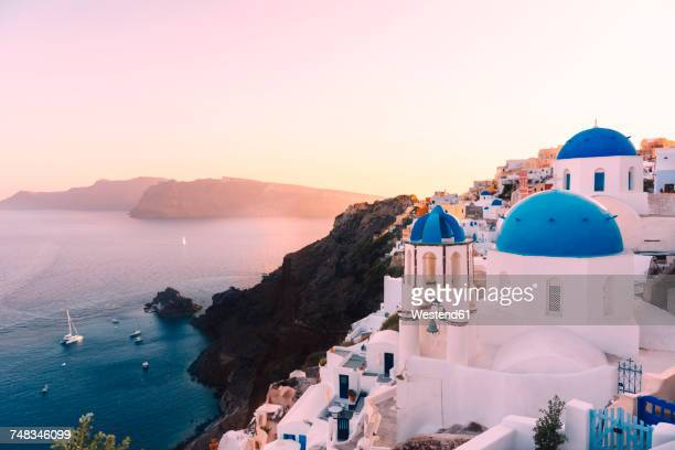 Greece, Santorini, Oia, view to caldera and Greek Orthodox Church at sunset