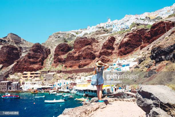 greece, santorini, oia, woman enjoying the view in the fishing harbor with the white village above the cliff - europe stock pictures, royalty-free photos & images
