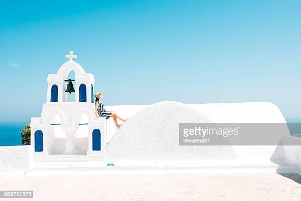Greece, Santorini, Oia, woman sitting on spur of belltower
