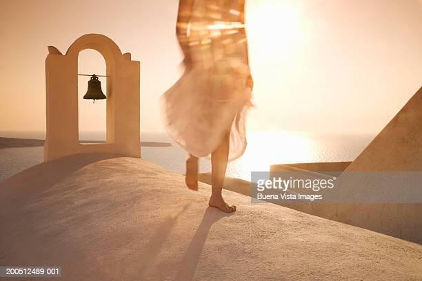 Greece, Santorini, Oia, woman walking, low section, sunset