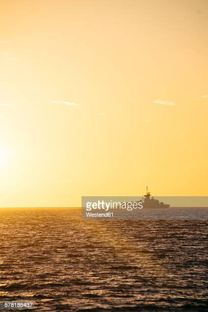 Greece, silhouette of warship at horizon seen from Paros by sunset