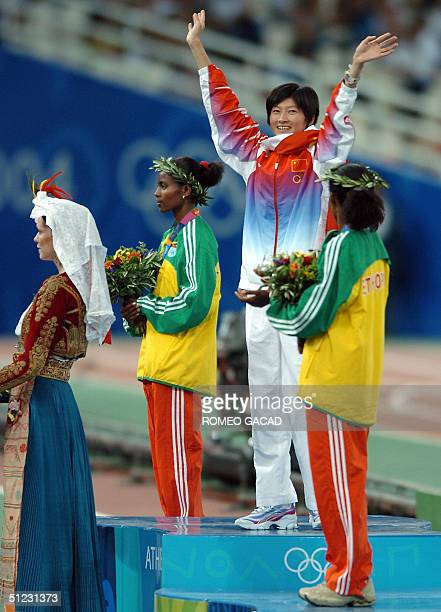 Silver medalist Ethiopia's Ejegayehu Dibaba gold medalist China's Xing Huina and Ethiopia's Derartu Tulu celebrate on the podium of the women's...