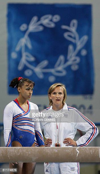 Soraya Chaouch of France chats with an unindentified staff member after not being qualified for the women's Artistic Gymnastics final 15 August 2004...