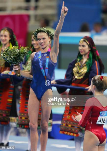 Svetlana Khorkina of Russia waves after receiving the silver medal as gold medallist Carly Patterson of the US looks on at the end of the Women's...