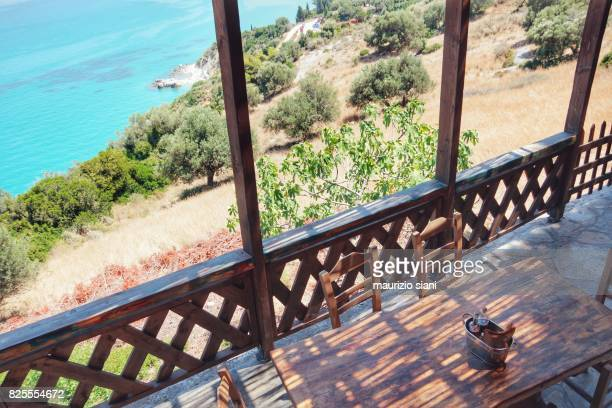 Greece, table and chairs of taverna against sea