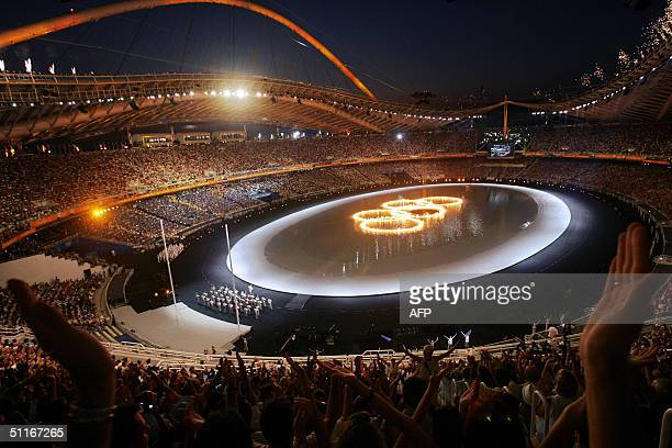 The five Olympic rings are lit with fire in a pool in the Athens Olympic Stadium during the 2004 summer games opening ceremony, 13 August 2004. Some...