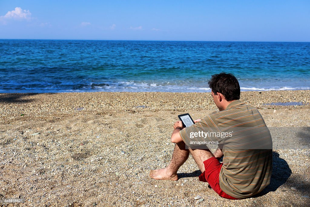 Greece, Thessaloniki, Man reading e-reader on beach : Stock Photo