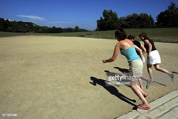 Tourists race in the ancient stadium of Olympia where the Olympic Games were born in 776 BC 07 August 2004 Ancient Olympia about 325 kilometers west...