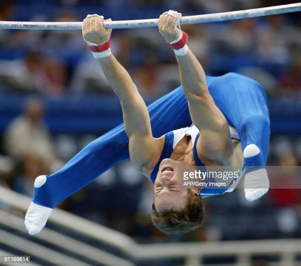 Paul Hamm performs on the uneven bars 14 August 2004 at the Olympic Indoor Hall during the men's gymnastics artistic qualification of the Athens 2004...