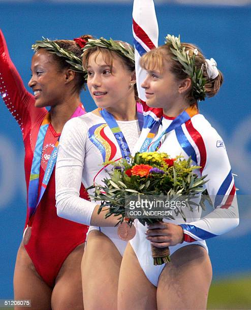 US silver medallist Annia Hatch Romanian gold medallist Monica Rosu and Russian bronze medallist Anna Pavlova celebrate on the podium after the...