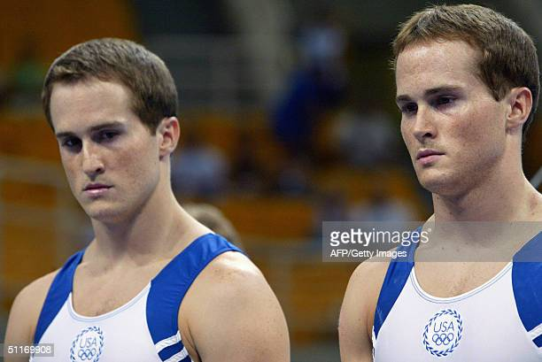 Twins gymnasts Paul and Morgan Hamm concentrate 14 August 2004 at the Olympic Indoor Hall during the men's gymnastics artistic qualification of the...