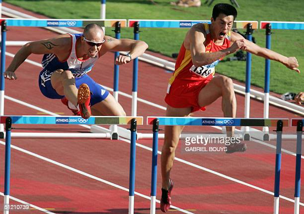 USA's Dean Macey and China's Qi Haifeng compete in the men's decathlon 110m hurdles heats at the Olympic Stadium 24 August 2004 during the Olympic...