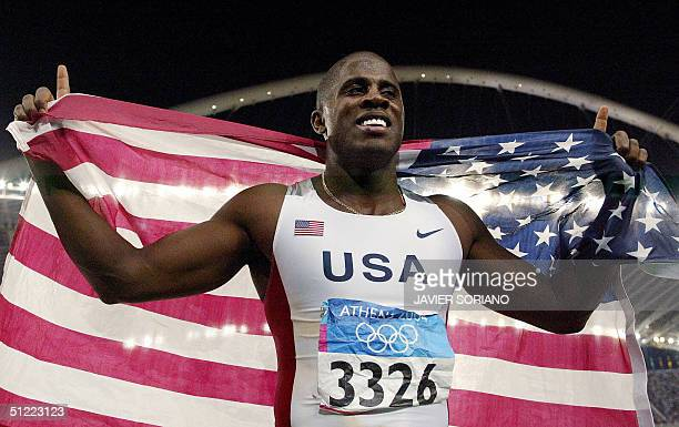 USA's Dwight Phillips celebrates with their country's flag after the men's long jump final at the Olympic Stadium 26 August 2004 during the Olympic...