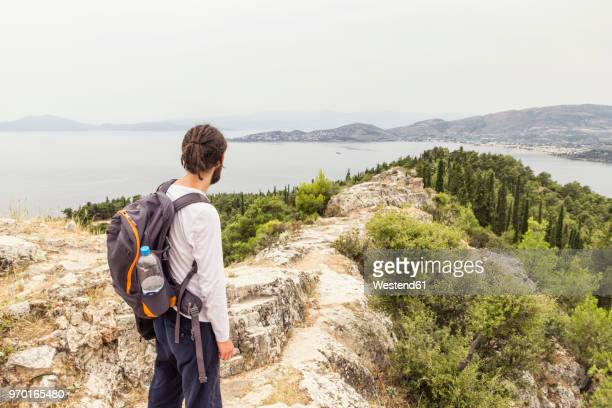 greece, volos, man enjoying view to pagasetic gulf - volos stock pictures, royalty-free photos & images