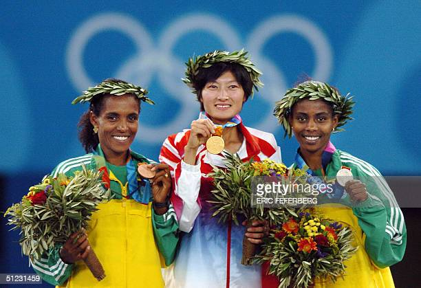 Women's 10000m gold medal winner Xing Huina of China Ethiopians silver medal winner Ejegayehu Dibaba and bonze winner Derartu Tulu stand on the...