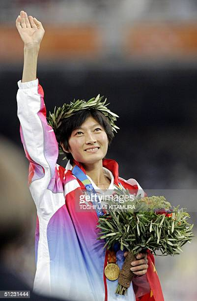 Women's 10000m gold medal winner Xing Huina of China stands on the winner's podium 28 August 2004 during the Olympic Games athletics competitions at...