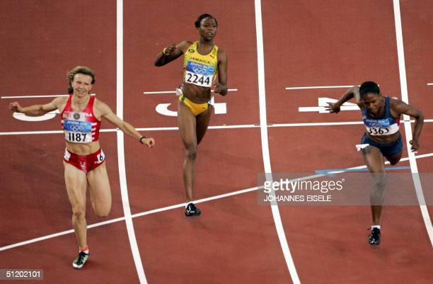 Yuliya Nesterenko of Belarus Lauryn Williams of the US and Sherone Simpson of Jamaica compete in the women's 100m finals 21 August 2004 during the...