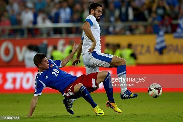 Greece's Alexandros Tziolis fights for the ball with Liechtenstein's Sandro Wieser during their 2014 World Cup qualification game at the Karaiskaki...