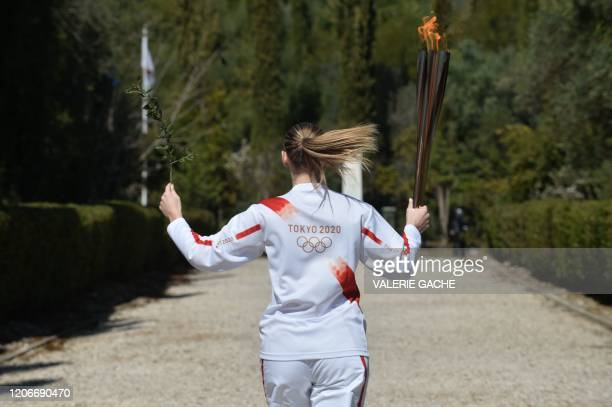 Greece's Anna Korakaki Rio 2016 gold medallist in the 25m pistol shooting runs with the Olympic flame and an olive tree during the Olympic flame...