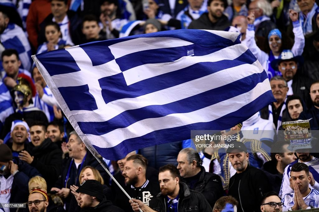 Greece's fans wave the Greek national flag during the World Cup 2018 qualifying football match Belgium vs Greece on March 25, 2017 at the King Baudouin stadium in Brussels. / AFP PHOTO / Belga / YORICK JANSENS / Belgium OUT