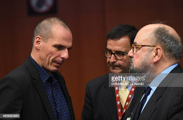 Greece's Finance Minister Yanis Varoufakis speaks with Greek delegation members during an Eurogroup finance ministers meeting at the European Council...