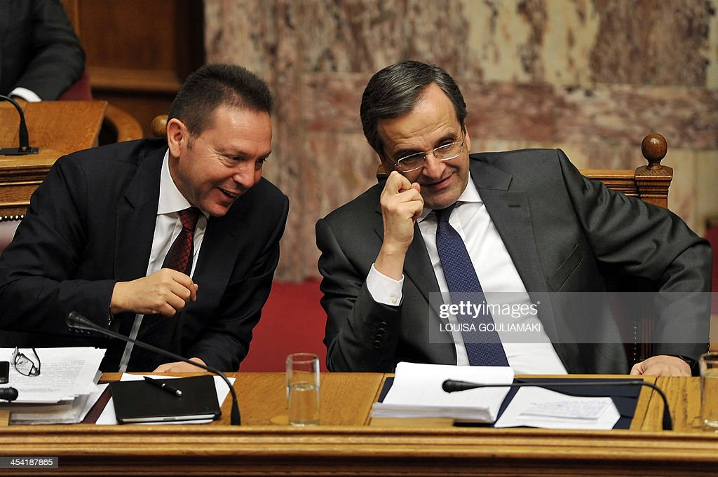 Greece's Finance Minister Yannis Stournaras (L) and Prime Minister Antonis Samaras attend a parliamentary session before voting on the 2014 budget in Athens on December 7, 2013
