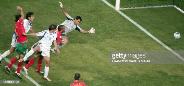 Greece's forward Angelos Charisteas heads the ball to score against Portugal despite Portuguese goalkeeper Ricardo 04 July 2004 at Stadio da Luz in...