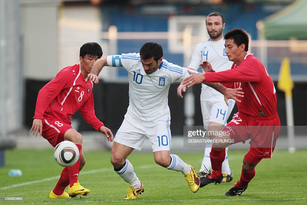 Greece's Georgios Karagounis (2nd L) and Dimitrios Salpingidis (2nd R) fight for the ball with North Korea's Yun Nam Ji (L) and Yong Hak An (R) during a friendly football game in Altach, on May 25, 2010 ahead of their participation to the FIFA World Cup 2010 in South Africa.