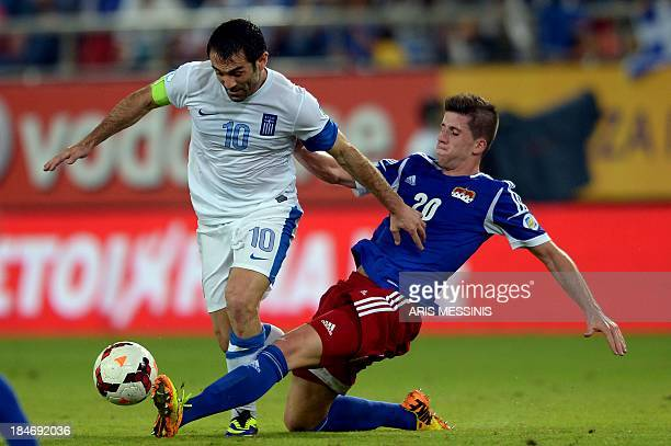 Greece's Giorgos Karagounis fights for the ball with Liechtenstein's Sandro Wieser during their 2014 World Cup qualification game at the Karaiskaki...