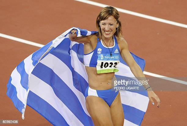 Greece's Hrysopiyi Devetzi celebrates after winning the bronze medal in the women's triple jump final at the 'Bird's Nest' National Stadium during...