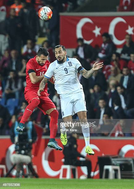 Greece's Kostas Mitroglou jumps for a ball with Turkey's Mehmet Topal during an international friendly soccer match between Greece and Turkey...