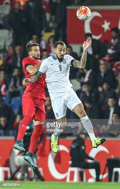 Greece's Kostas Mitroglou jumps for the ball with Turkey's Mehmet Topal during an international friendly soccer match between Greece and Turkey...