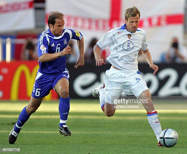 Greece's midfielder Angelis Basinas fights for the ball with Russian midfielder Andrei Karyaka 20 June 2004 during their European Nations...