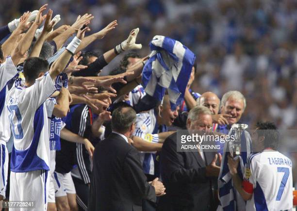 Greece's midfielder Theodoros Zagorakis receives the trophy from UEFA chairman Lennart Johansson 04 July 2004 at the Luz stadium in Lisbon after the...