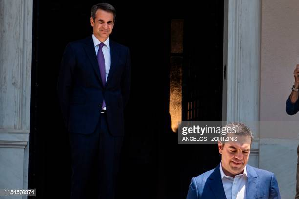 TOPSHOT Greece's new conservative Prime Minister Kyriakos Mitsotakis watches his predecessor Alexis Tsipras leaving the Maximos Mansion after their...