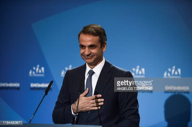 TOPSHOT Greece's newly elected Prime Minister and leader of conservative New Democracy party Kyriakos Mitsotakis reacts as he gives his first...