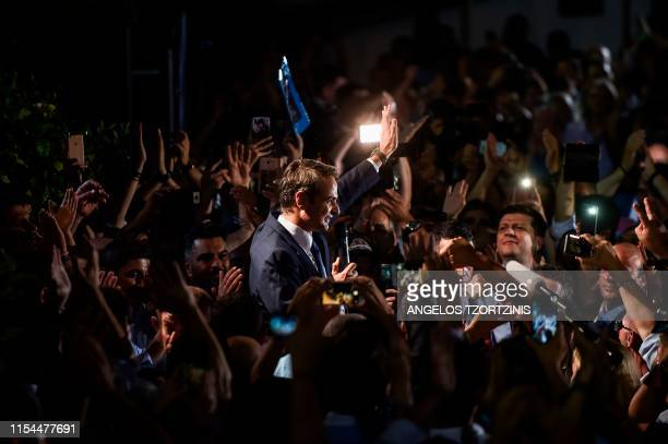 TOPSHOT Greece's newly elected Prime Minister and leader of conservative New Democracy party Kyriakos Mitsotakis waves at his supporters outside the...