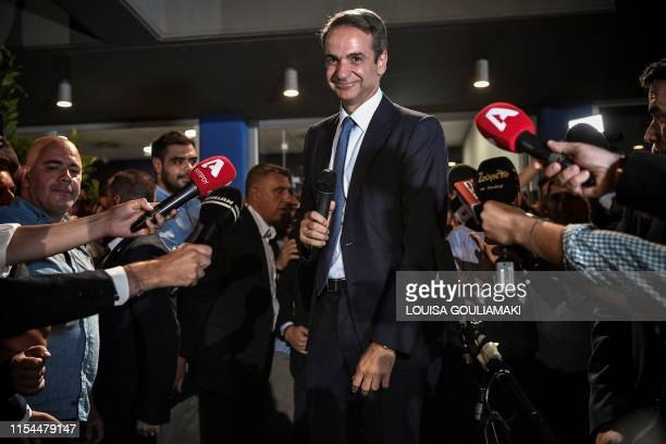 TOPSHOT Greece's newly elected Prime Minister and leader of conservative New Democracy party Kyriakos Mitsotakis speaks to the press outside the...