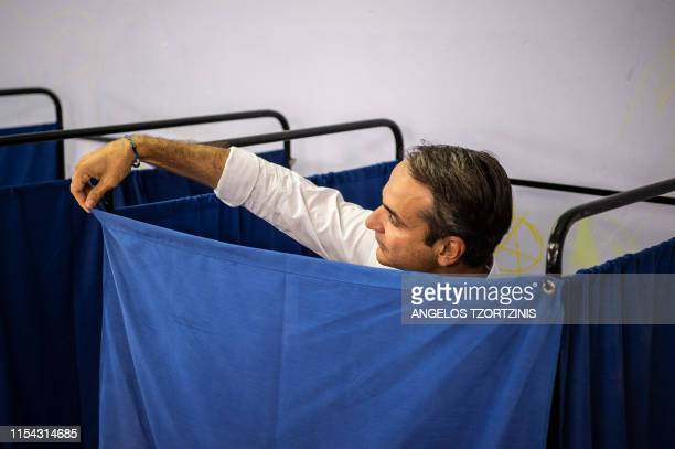 TOPSHOT Greece's opposition party New Democracy leader Kyriakos Mitsotakis stands in a polling booth prior to casting his vote during general...